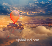 A red balloon, filled with helium, floats high above the clouds at sunset in this picture about freedom, adventure and possibilities.