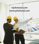 Picture of two men in hard hats looking out an office window and pointing. They have clipboards and one is taking notes as the other contractor points and talks. Picture of men working in hard hats for ads.