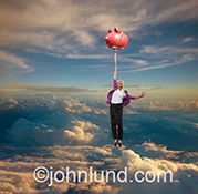A senior woman floats high into the sky holding on to a large piggy bank in a stock photo about retirement planning, investment and savings.