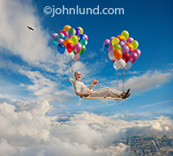 A senior man floats through the clouds on a lounge chair supported by balloons in a concept photo about retirement issues, retirement investing and leisure activities.