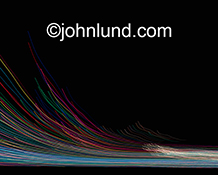 Colored light trails streak across a black background and arch upwards in this stock photo about communications technology, wireless communications, bandwidth and networking.