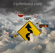 Numerous road signs emerge from a heavy and stormy cloud cover in a concept stock photo about the challenges, problems and confusion facing such a new technology despite the technologies overwhelming promise.