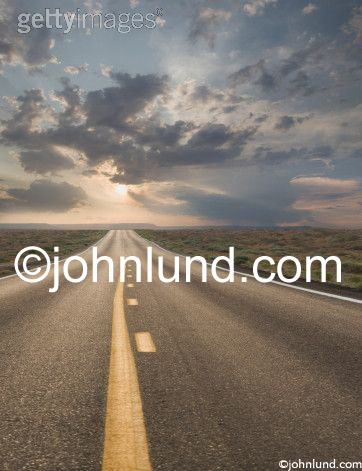 Concept Stock photo of a road stretching into the distant at sunrise or sunset and showing journeys, freedom, the way forward and the future.