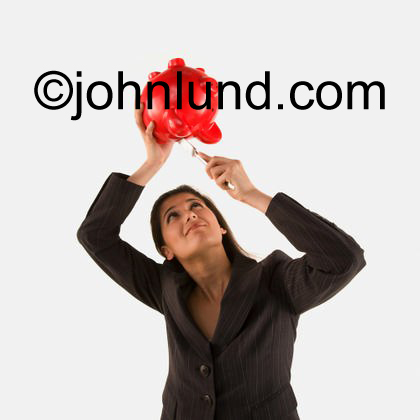 Stock photo of an ethnic woman using a knife to pull coins out of a bright red piggy bank in an illustration of personal financial challenge.
