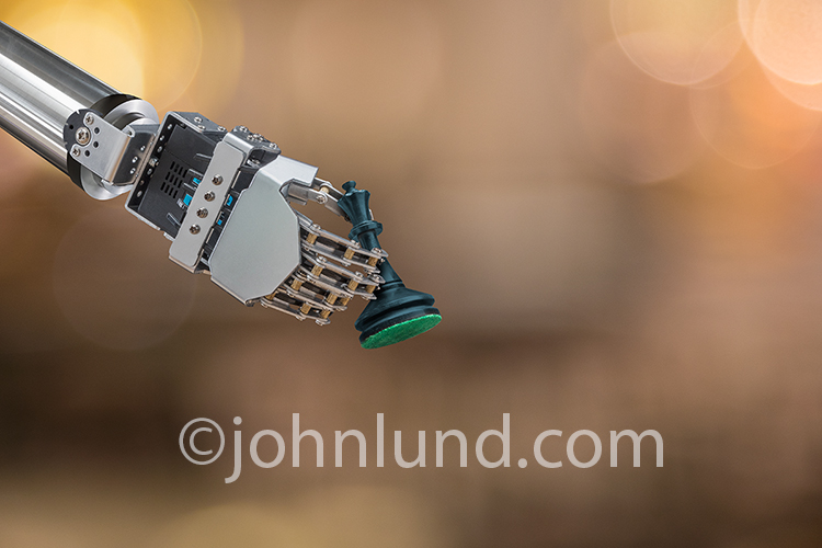 A robot's hand holds the Queen chess piece in a stock photo about robotics, artificial intelligence, and the future.