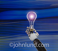 A robot hand holds up a glowing lightbulb in a stock photo about robotics, artificial Intelligence, and innovation.