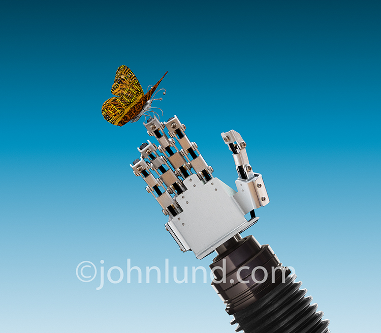 A robot butterfly alights on a robot hand in a stock photo about robotics, future technology, and artificial intelligence.