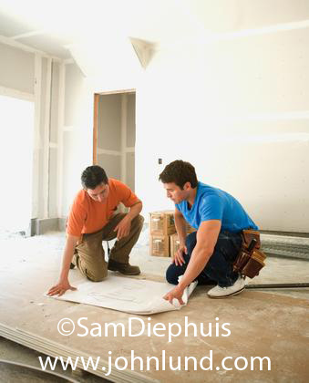 Picture of two caprenters looking at blueprints they've rolled out onto the floor to look at. One man is wearing an orange shirt and the other a blue shirt. The prints are on a short stack of sheetrock.
