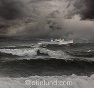 A ship crests a wave in rough seas under dark and stormy clouds in a stock photo about danger, risk, adventure and so much more.