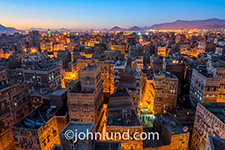 The old city of Saana, Yemen photographed at a high elevation at dusk with the city lights just coming on adding a golden orange glow to the streets and buildings.