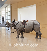 A saddled rhino, standing in an upscale corporate lobby, presents a business challenge in a stock photo about conquering adversity, with daring and courage even when facing unusual problems, risks, and danger.