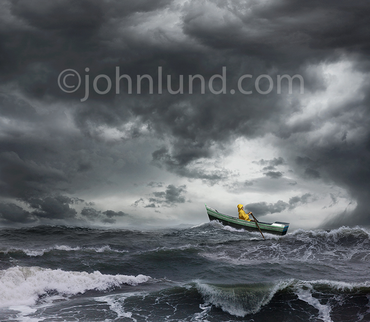 A sailor rows a small boat through rough seas in an ocean storm in this stock photo about risk, danger, courage and daring in the face of overwhelming challenges.