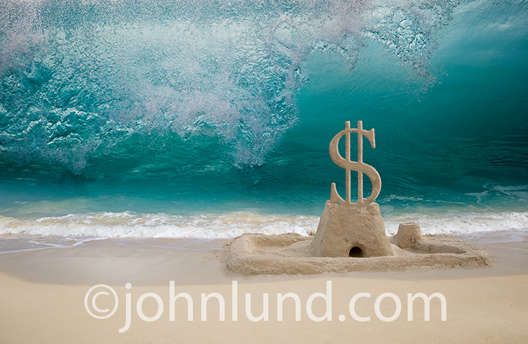 A dollar sign sand castle is about to be inundated by a huge ocean wave in a stock photo about financial risk, danger and investment issues.