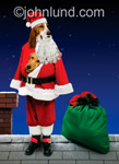 Funny picture of dogs dressed as Santa Claus with a bag of gifts standing on a roof top.