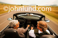 Senior couple on a road trip in a convertible sports car with the top down. She has gray hair and she is looking at him. He is the passenger and is looking at her. Driving fast pic.