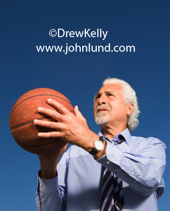 Picture of an older senior man with gray hair and a gray goatee is holding a basket ball in his hands and he is about to shoot some hoops. Senior man playing basketball.