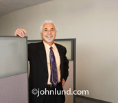 Photo of a handsome happy older businessman standing next to an office cubicle. The business man is smiling at tlhe camera and has gray hair and a gray goatee. He is wearing a business suit and tie. Stock photo of a businessman.