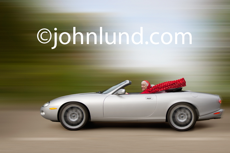 In this picture a senior white-haired woman drives a speeding convertible sports car through the countryside while she wears a bright red scar blowing in the wind.