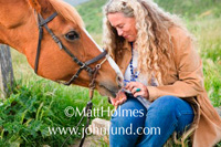 A mature or senior woman is feeding her horse from her hand.  The woman is older with long curly blonde/gray hair and she is smiling.  Beautiful horse picture. Woman is wearing blue jeans. Horse is wearing a bridle.  Reins hanging down.