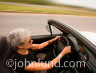 Gray haired senior woman of hispanic descent is driving a sports car with the top down. Side view of woman driving a sports car. Seniors driving fast.