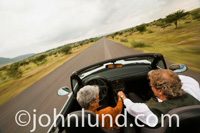 Photo of a senior couple driving a convertible sports car with the top down on a country road. The woman is driving and has short gray hair.  Both seniors have their hands on the gear shift lever. Seniors driving fast pic.