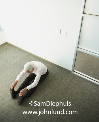 Picture of a white haired gentleman sitting on the floor of an empty office and stretching by touching his toes. Business executive doing a stretching routine on his office floor.