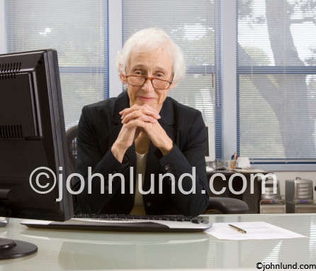 Picture of senior business woman executive sitting at a desk; a benevolent looking woman, vital and wise from her years of experience. She is smiling at the camera, looking at it over the top of her reading glasses.