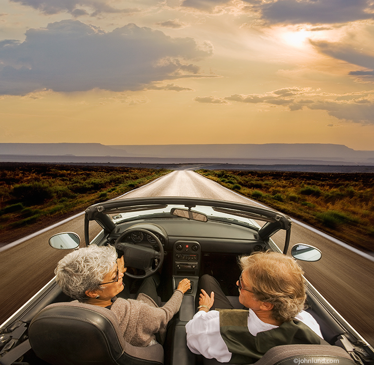 Successful seniors on a road trip in a convertible sports car is the subject of this photo featuring a mature man and woman speeding down a wide-open road to the future.