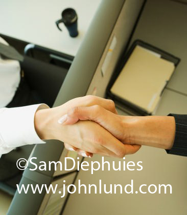 Picture of a handshake.  Two hands shaking over the cubicle wall. A man's hand and a woman's hand shaking over a cublicle to seal an agreement. Photo of a business handshake.