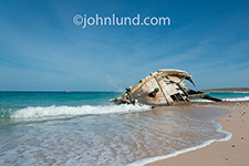 The shattered hull of a ship wreck rests in the surf on a beach on Socotra Island, yemen in an image about risk, danger and aftermath.