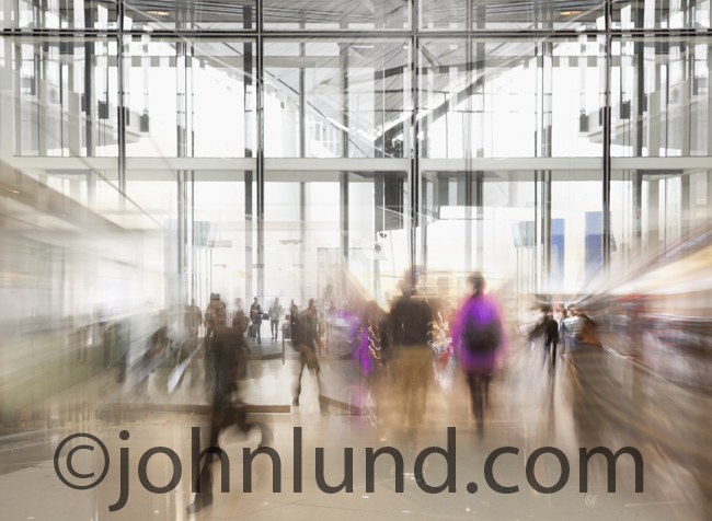 A busy modern shopping mall is represented by this futuristic image with people in motion in a bast building of glass.
