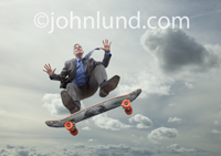 Picture of a senior man in business attire performing tricks on a skateboard the underside of which has a money graphic design.