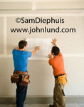 Stock photo of a couple of skilled carpenters looking at blueprints that they are holding up against a wall. One man has a blue shirt and the other man has on an orange shirt. Both workers are wearing toolbelts. Contractors in action.