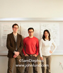 Stock photo of three individuals standing together in front of a white board looking at the camera. The three young business people are in a start-up or perhaps a dot com enterprise.  Happy successful young entreprenuers.