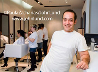Portrait style picture of a smiling happy man in a hair salon leaning against the wall. Behind the man is a row of beauticians or hair stylists doing women's hair. Owner small business. Small business advertising photos.