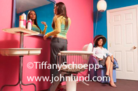 A young woman is checking her makeup in a mirror on the wall of a beauty salon.  The wall is pink. Another lady is under a hair dryer in the corner of the room. Beauty salon photo.