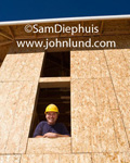 Picture of a construction worker looking out of a second floor window of a large unfinished building under construction. Ad pictures for new construction and building supplies and services. Friendly builders pictures.
