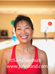 This happy Japanese woman is standing in the gymnasium with her hair pulled back and wearing a red tank top. She has been working out and perhaps playing some pick up basketball. Healthy and fit this woman leads a healthy lifestyle.
