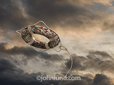 A life ring, or life preserver, flies towards the viewer through stormy skies in this image about being rescued by the crowd using social media and networking in this stock photo.