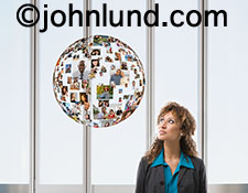 The world of social media is illustrated with this image showing a woman looking up to a sphere of portraits, a sphere that symbolizes the world of online social interactions.