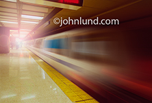 A speeding metro transit train streaks by in a blur at an underground station of an unnamed city.