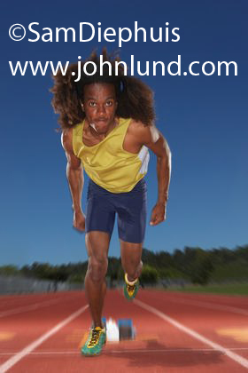 Black male athlete, a sprinter,  leaving the starting blocks with a big Afro type hairstyle. He is determined to win!  Bright yellow jersy and blue running shorts with green shoes.  Determination strength effort pic.