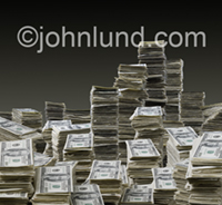 Stacks of money (dollars, currency, cash) piled high (tall stacks of money) featuring 100 dollar bills in a business concept stock photo.