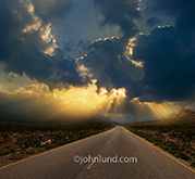 A road stretches off towards a stormy sky with god rays emanating for dark storm clouds in an image about the way forward, challenges and opportunities.