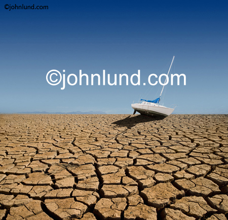 Picture of a sail boat stranded on dry cracked earth, run aground by some ecological disaster of drought and water scarcity. Picture of a dried up lakebed. Picture of a sailboat stranded on land.