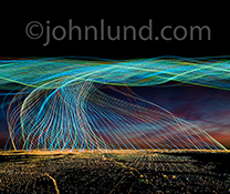 Big data streams from and over a city at night in a communications technology stock photo featuring color light trails representing streaming data as they flow from and to a city at night.