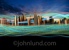 Streaming data, communications technology, big data collection and management, and connections are all illustrated in this colorful and dynamic stock photo featuring light trails flowing over and around high rise buildings in a large city.