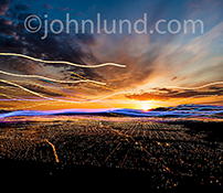 This stock photo of streaming data over a networked city at sunrise combines a dramatic portrayal of a difficult concept (networking, connections and streaming data) along with the incredible beauty of a mountain sunrise over city lights.