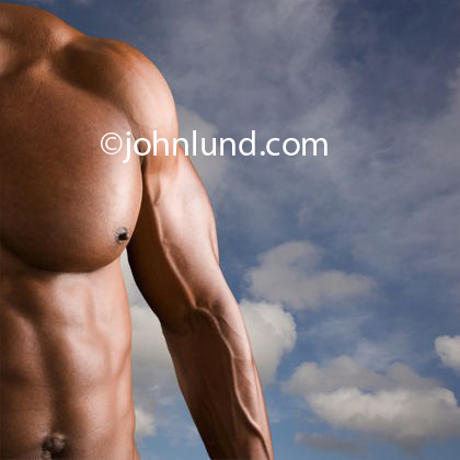 Stock photo of a really ripped defined muscular mans chest and arm.  Partial torso of a muscle bound man.  Blue sky with clouds background to a bare chested muscular mans torso for ads. Body builder pics.