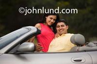 Man hugging his girl friend in the front seat of his convertible with the top down.  She is wearing a bright red blouse and he is wearing a yellow shirt.  Handsome and beautiful.  Romantic car pic.